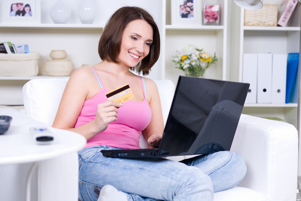 Beauty woman holding credit card and using laptop for online shopping - indoors